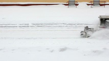Driver on a red traktor clears road of snow in winter