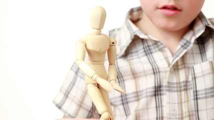 boy makes wooden figure of human scratchs its head