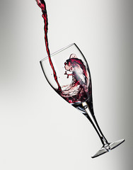 Red wine being poured into floating glass