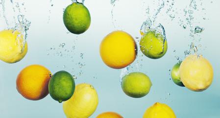 Lemons and limes splashing in water