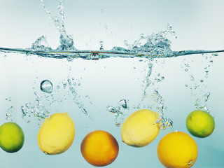 """Lemons, limes and oranges splashing in water"""