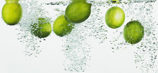 Limes splashing in water
