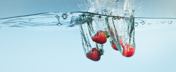 Strawberries splashing in water