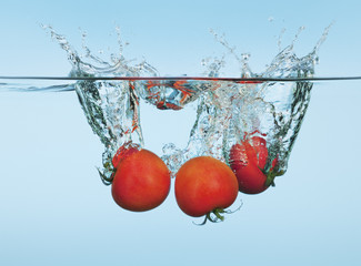 Tomatoes splashing in water