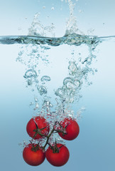 Tomatoes on vine splashing in water