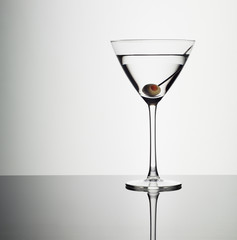 Martini in glass with green olive