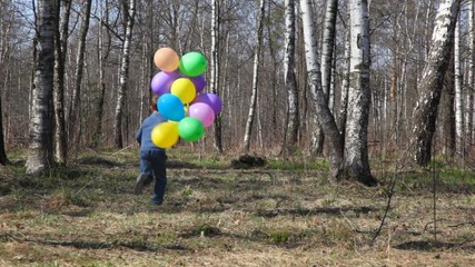 boy with balloons runs to forest from camera, then comes back