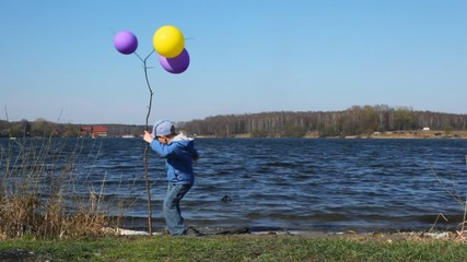 boy on coast near young tree with balloons looks at lake