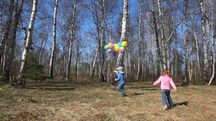 boy holds bunch of balloons and girl runs around in forest