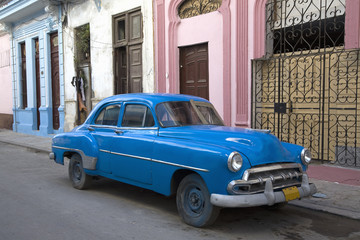 1950s Chevrolet sedan parked on dilapidated street