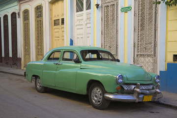 1950s car parked on dilapidated street
