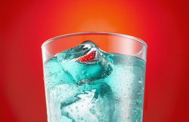 Close up of blue soda in glass with ice cubes