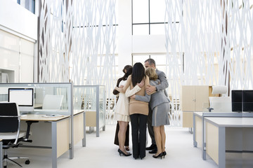 Business people huddling in modern office