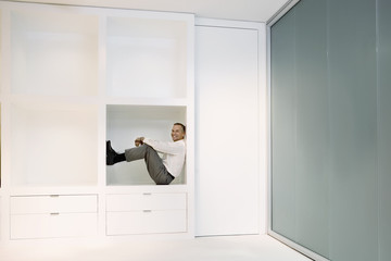 Businessman crouching in office shelf