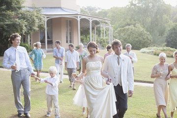 """Bride, groom and guests walking across lawn"""