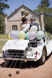 Mature bride and groom riding in convertible