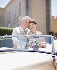 Mature bride and groom in convertible