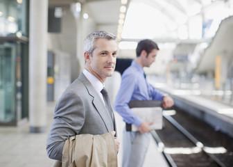 Businessmen waiting for train on platform