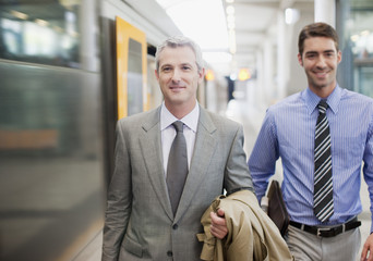Businessmen walking on train platform