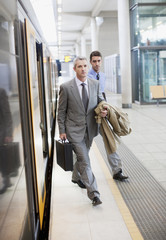 Businessmen exiting train at train station