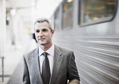 Businessman walking on train platform