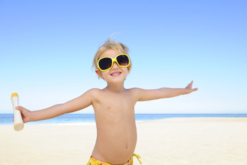 happy child with sunglasses and suntan lotion