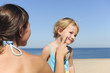 Mother applying suntan lotion to her daughter
