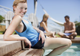 Woman reclining at swimming pool?s edge