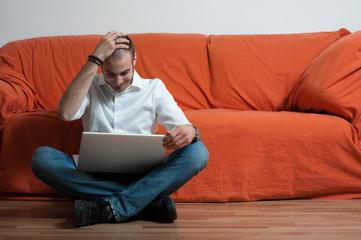 uomo disperato seduto vicino a divano con computer