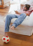 Man laying on sofa watching television