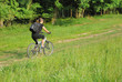 woman riding a bike on a road in forest with a bit motion blur