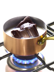 melting pieces of chocolate in milk in a copper saucepan