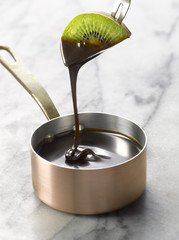 dipping a slice of kiwi into a saucepan of melted chocolate