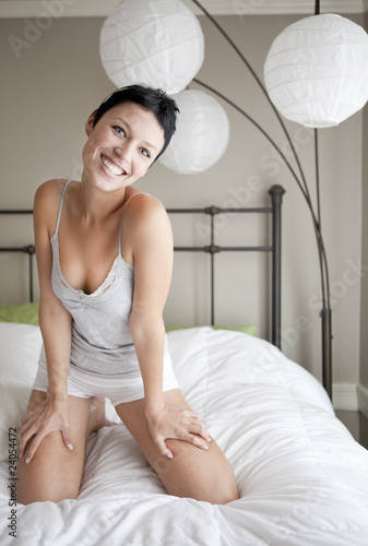 Woman kneeling on bed