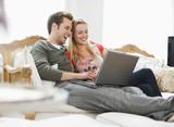 Couple using laptop on sofa