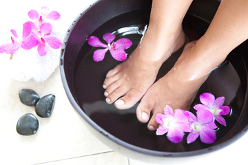 Feminine feet in foot spa bowl with orchids