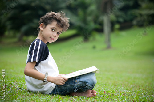 Young boy enjoying his reading book in outdoor park