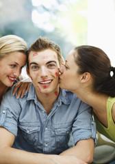 Women leaving lipstick kisses on man