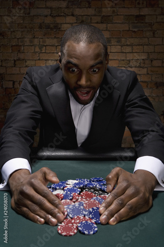 Man gathering poker chips in casino