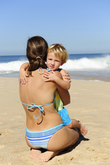 Happy child hugging her mother on the beach