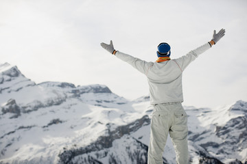 Man with arms outstretched on mountain top
