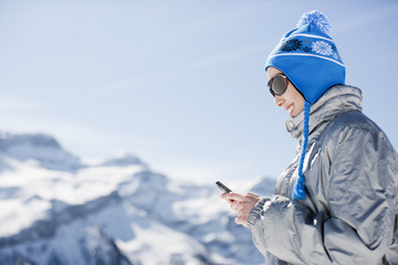 Woman using cell phone on mountain top