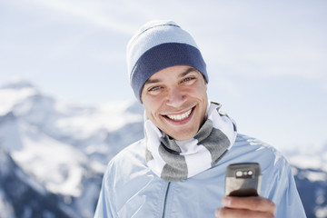 Man using cell phone on mountain top