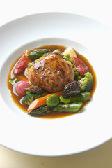 stuffed veal caillette with gravy and spring vegetables