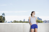 Woman leaning against concrete wall after exercise