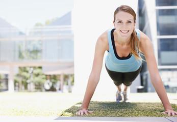 Woman doing push-ups in urban setting