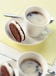 chocolate and hazelnut shortbread biscuits filled with sugar ganache and cups of coffee