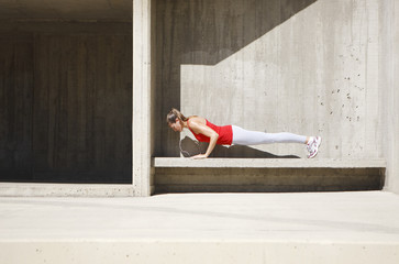 Woman doing push-ups on concrete bench