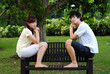 Young Asian Couple in Love sitting on edge of bench