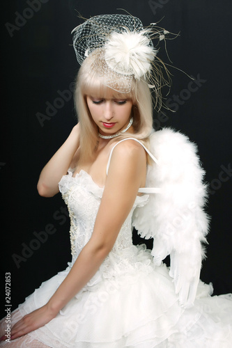 beautiful blonde in an extravagant hat and white dress with wing